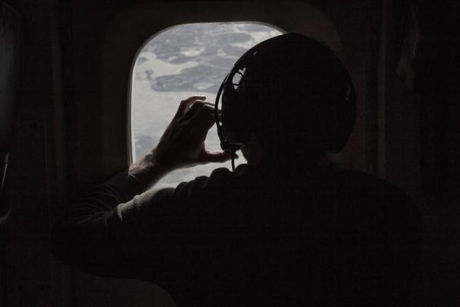 Researcher photographing the sea ice as the DC-8 flies over the Arctic January 2017. Credits: NASA / National Center for Atmospheric Research / Sam Hall